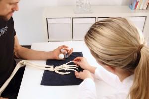 Handchirurg unterstuetzt Patient mit Bällen