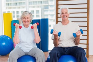 Happy senior couple lifting dumbbells on exercise ball